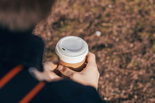 person person holding white and brown cup finger