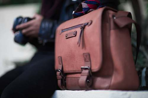 person selective focus photogrtaphy of brown leather crossbody bag people