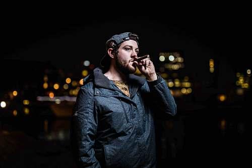 person standing man in black zip-up jacket smoking face