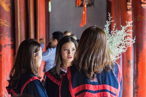 person three women having conversation inside building academic gown