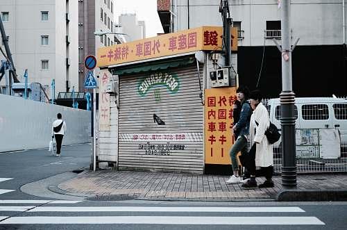 person two women walking near street post and pedestrian lane people