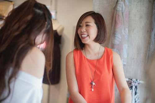 person woman in orange tank top smiles beside woman asian teacher