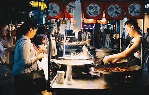 person woman standing in front of food stall clothing