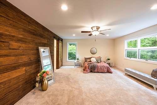 appliance empty bedroom with turned-on lights ceiling fan