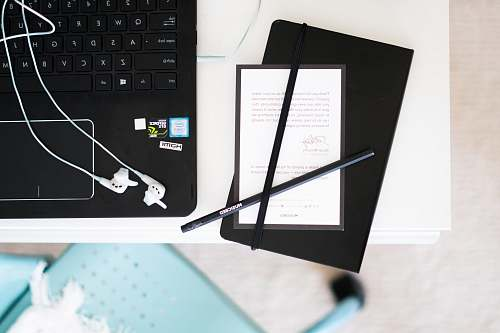 laptop black pens beside laptop computer placed on table flatlay