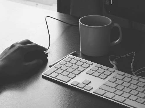 photo black-and-white grayscale photography of person holding computer mouse near keyboard and mug grey free for commercial use images