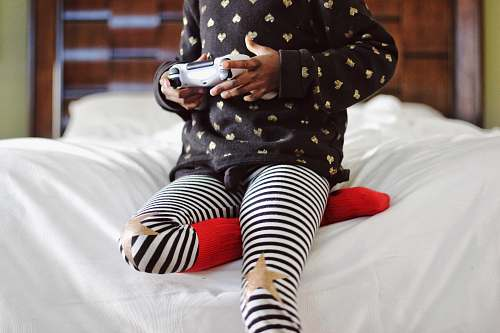 games children holding gray game controller sitting on white bed children