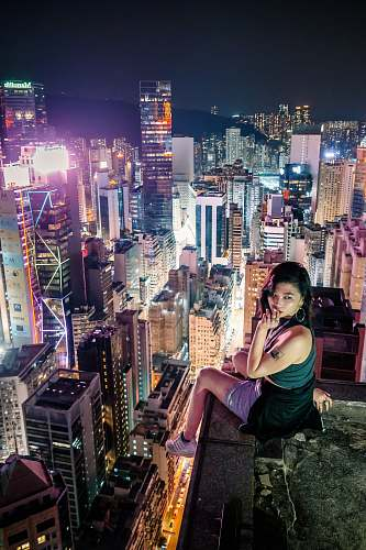 nature woman sitting on a terrace overlooking an urban city at night outdoors