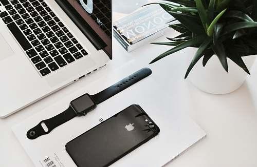 work space black stainless steel Apple Watch on table beside the MacBook Pro desk