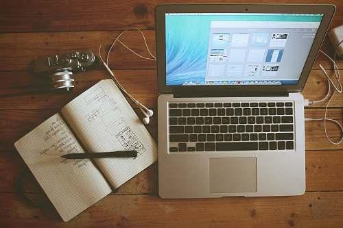 computer turned on MacBook Air beside white notebook wood