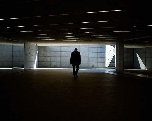 grey silhouette photo of person walking inside dark room piazza gae aulenti