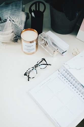 desk black framed eyeglasses beside spiral notebook work
