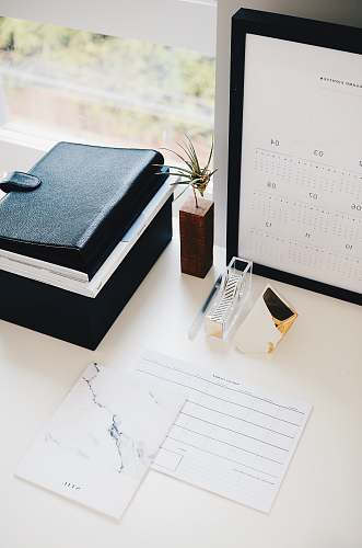photo desk books and calendar on white table plant free for commercial use images