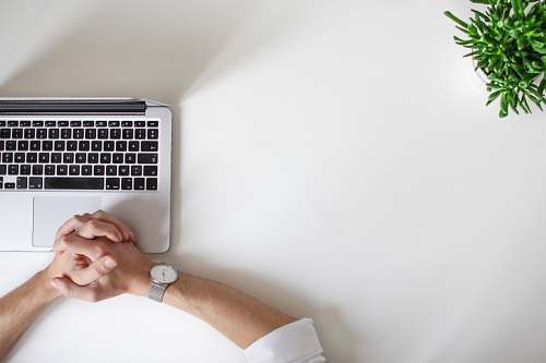photo desk person wearing watch near laptop plant free for commercial use images