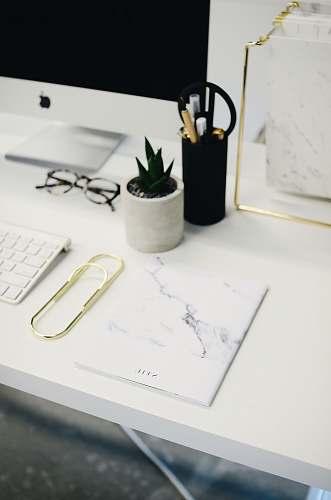 desk silver iMac and Magic Keyboard on ta ble near white printer paper work