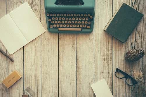 work vintage teal typewriter beside book desk