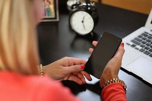 clock woman sitting holding smartphone near laptop phone