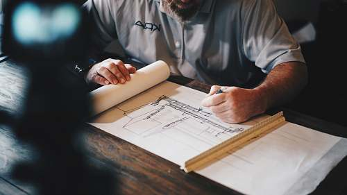 person An architect working on a draft with a pencil and ruler human