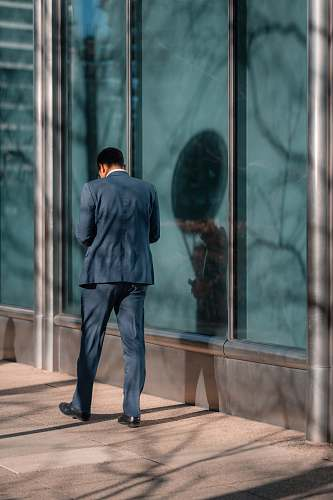 person man standing near glass wall human