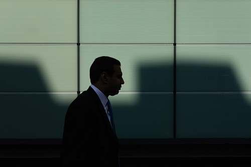person man walking near gray concrete wall human