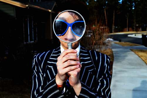 person person using magnifying glass enlarging the appearance of his nose and sunglasses magnifying glass