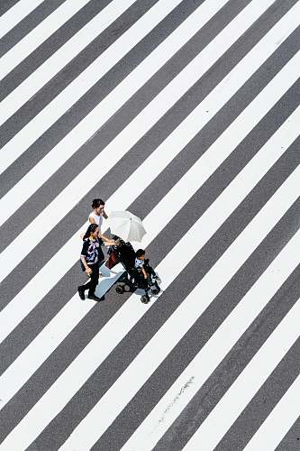 tarmac two women and baby crossing striped floor road