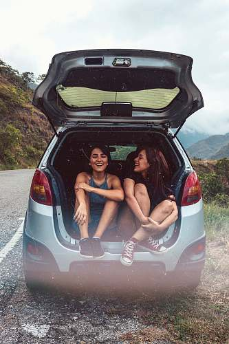 human two women in hatchback compartment person