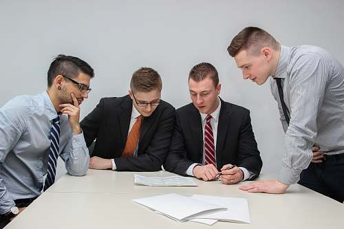 human four men looking to the paper on table sitting