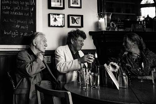 people grayscale photo of three man sitting beside table human