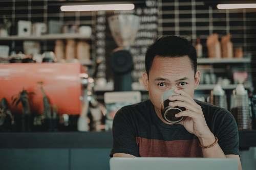 human man drinking on mug while sitting people