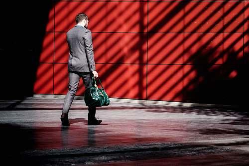 human man holding green duffel bag while walking near red building at daytime people