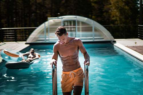 human man holding grey steel swimming pool ladder people