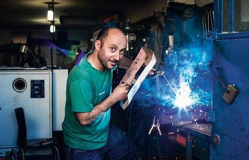 human man holding welding mask factory