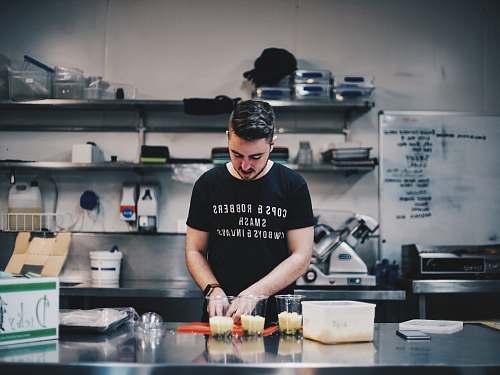 people man in black shirt beside kitchen table human