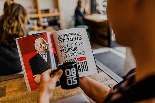 human man reading magazine book