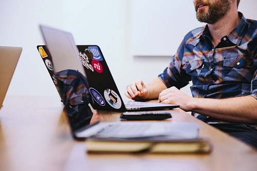 human man sitting in front of laptop people