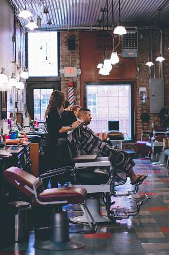 human man standing beside man sitting on barber chair people