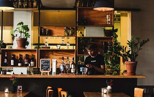 human man standing in front of bar table pub