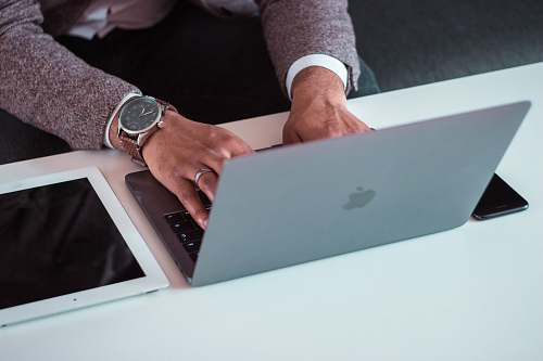electronics man using MacBook between iPad and iPhone wristwatch
