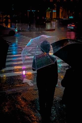human man wearing black suit jacket holding clear umbrella in front of pedestrian lane people