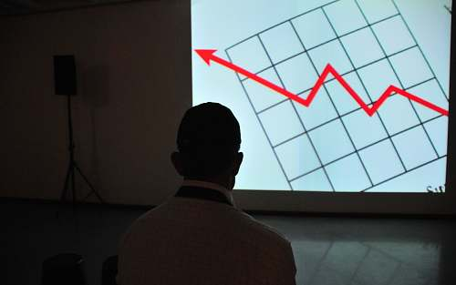 indoors man wearing white top looking at projector graph screen interior design