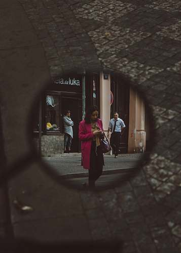 human mirror showing woman wearing pink coat walking on street people
