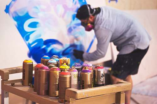 human paint sprays on table in front man painting on wall people