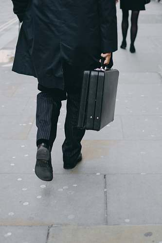human person carrying suit case while walking on pavement people