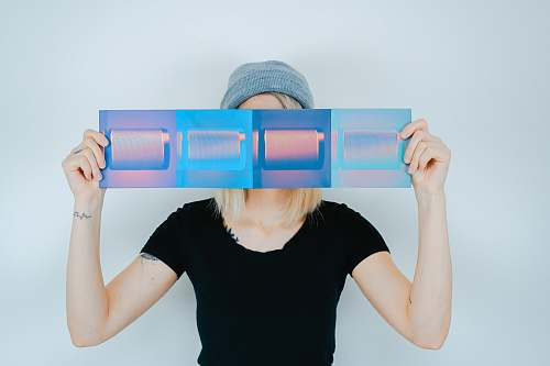 human person holding blue paper covering her face people