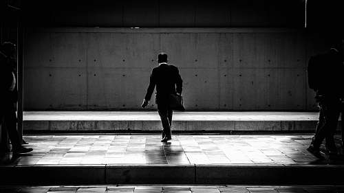 human person walking in the station black-and-white