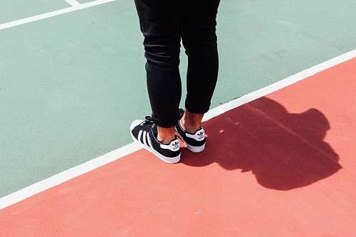 people person wearing black adidas sneakers human
