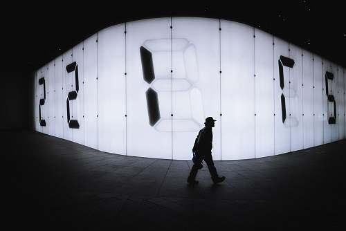 human photo of man walking near LED signage people