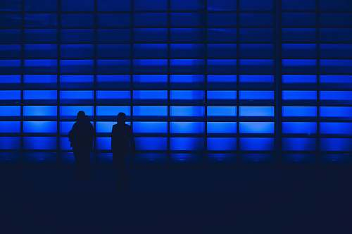 human silhouette photo of two person standing near wall silhouette