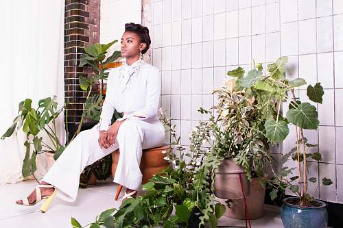 apparel sitting woman wearing withe long-sleeved shirt and pants surrounded by plants clothing